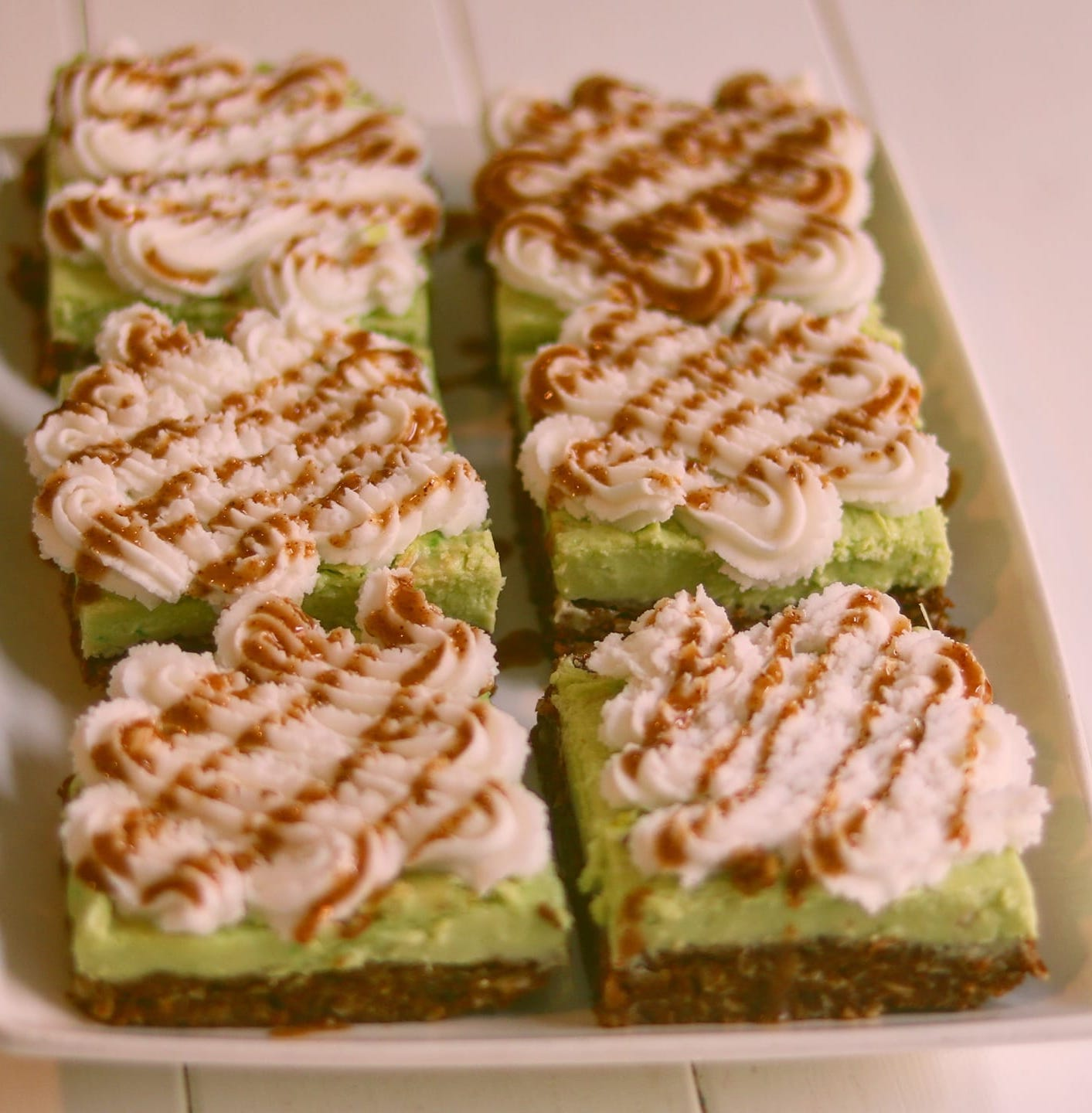 Giant Nanimo Bars with green middle, white frosting, caramel drizzle on top.